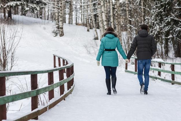 Jovem casal lindo andando na floresta de inverno Foto Premium