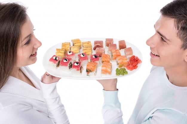 Jovem casal lindo está comendo sushi juntos. Foto Premium