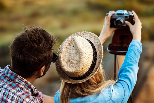 Jovem casal lindo fazendo selfie na câmera antiga, fundo do canyon Foto gratuita