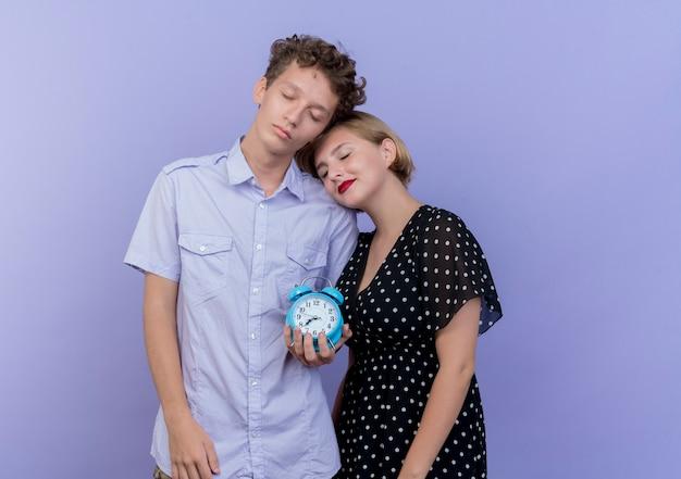 Jovem casal lindo feliz e apaixonado segurando o despertador sobre o azul Foto gratuita