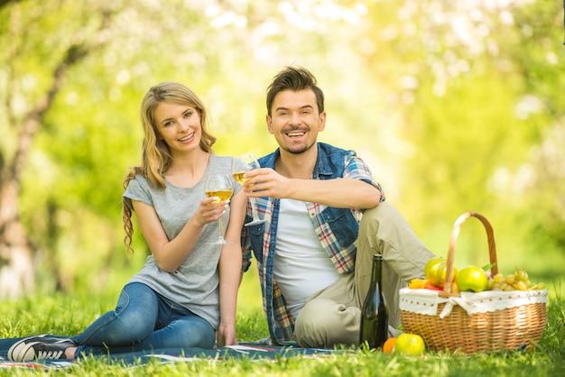 Jovem casal lindo no parque e bebendo vinho. Foto Premium
