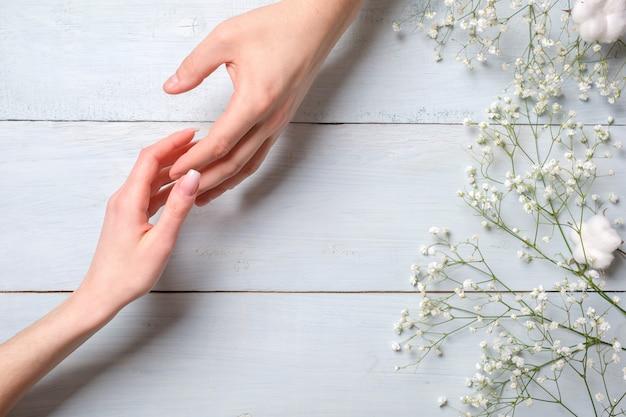 Jovem casal mão na mesa de madeira azul com flores Foto Premium