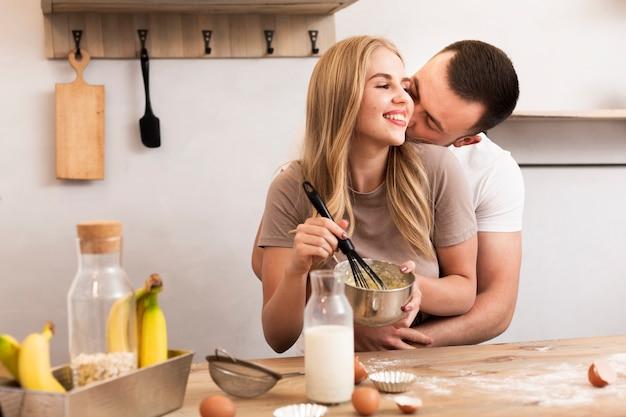 Jovem casal mexa ovos e leite na tigela Foto gratuita