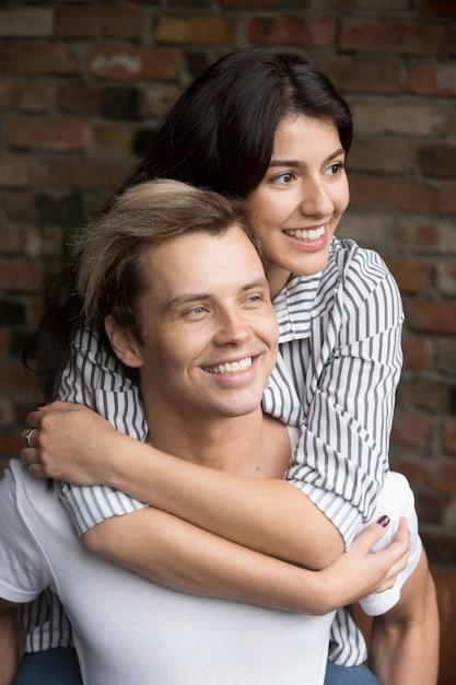 Jovem casal milenar no amor abraçando ansioso para o futuro Foto gratuita