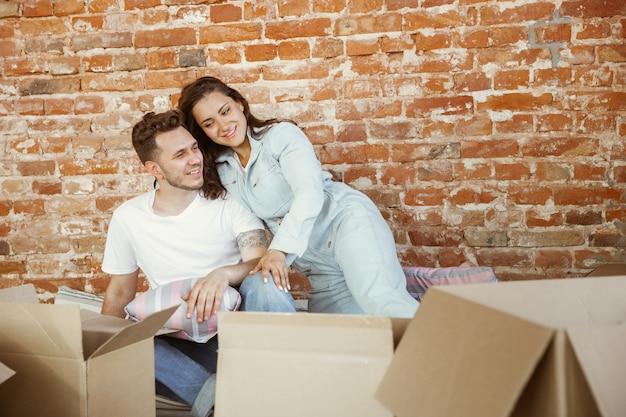 Jovem casal mudou-se para uma nova casa ou apartamento. deitados juntos, acariciando, abraçando, se divertindo no dia da mudança Foto gratuita