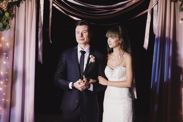 Jovem casal na cerimônia de casamento à noite. arco de casamento com lâmpada ao ar livre. Foto Premium