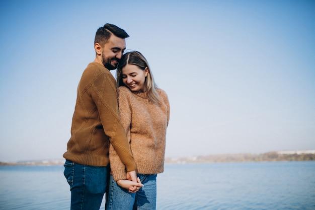 Jovem casal no parque em pé junto ao rio Foto gratuita
