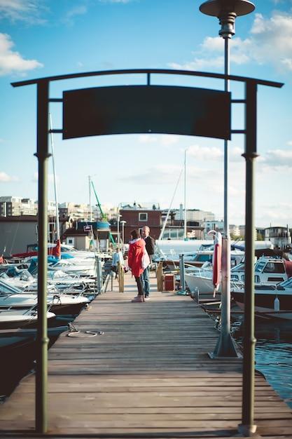 Jovem casal no porto de iates Foto gratuita