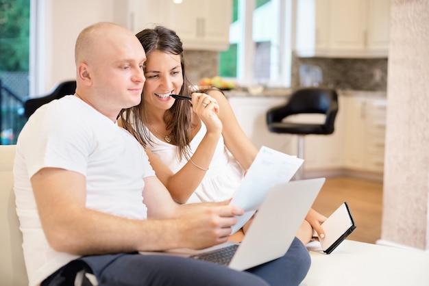 Jovem casal no sofá com o laptop e conta a conta para pagamento. o conceito de serviços públicos, dívida, pessoas e crédito. Foto Premium