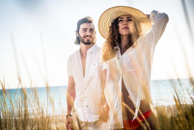 Jovem casal partilha feliz e amor humor na praia Foto Premium
