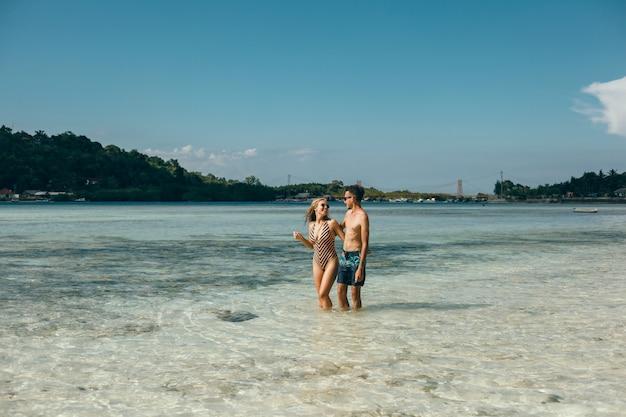 Jovem casal posando na praia, se divertindo no mar, rindo e sorrindo Foto gratuita