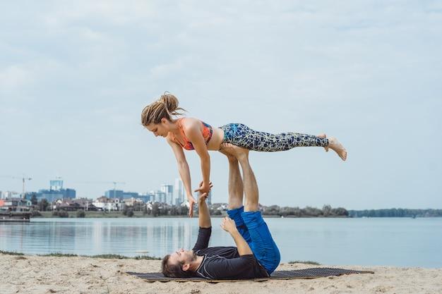 Jovem casal praticando yoga no fundo da cidade | Baixar