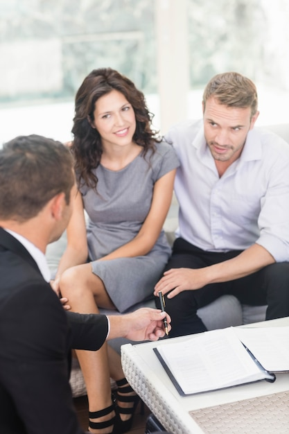 Jovem casal pronto para comprar casa nova interagindo com agente imobiliário Foto Premium