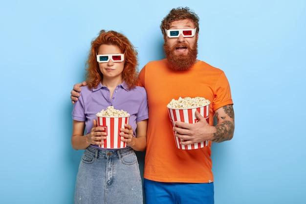 Jovem casal ruivo passa seu tempo livre no cinema 3d, come pipoca, usa óculos especiais para efeitos visuais, cara barbudo animado abraça namorada adorável que tem expressão entediada, não gosta de filme Foto gratuita