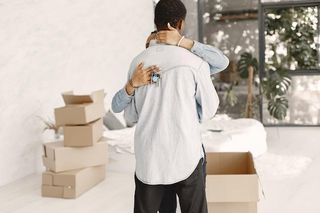 Jovem casal se mudando para a nova casa juntos. casal afro-americano com caixas de papelão. mulher segura as chaves. Foto gratuita