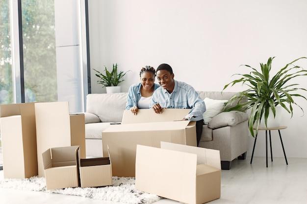 Jovem casal se mudando para a nova casa juntos. casal afro-americano com caixas de papelão. Foto gratuita