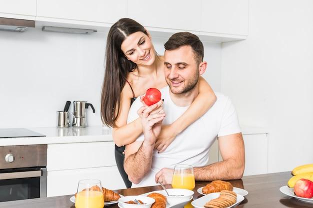 Jovem casal segurando a maçã na mão enquanto tomando café da manhã Foto gratuita