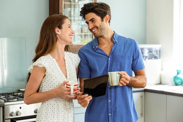 Jovem casal segurando a xícara de café enquanto estiver usando tablet digital Foto Premium