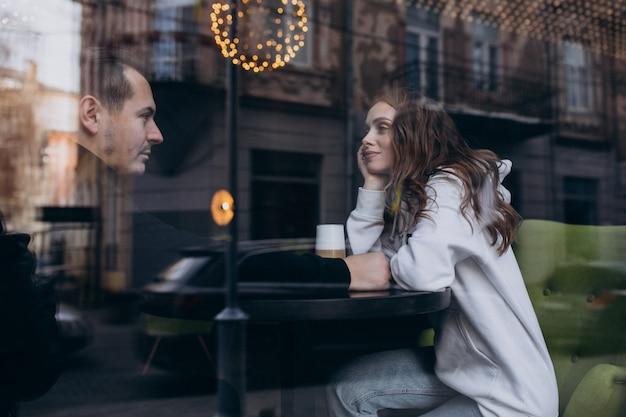 Jovem casal sentado em um café atrás da janela Foto gratuita