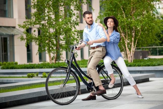 Jovem casal sentado em uma bicicleta Foto gratuita
