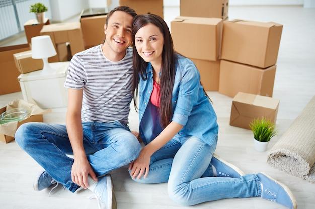 Jovem casal sentado no chão com caixas de mudança Foto gratuita