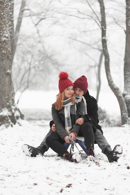 Jovem casal sentado no trenó e brincando com a neve Foto gratuita