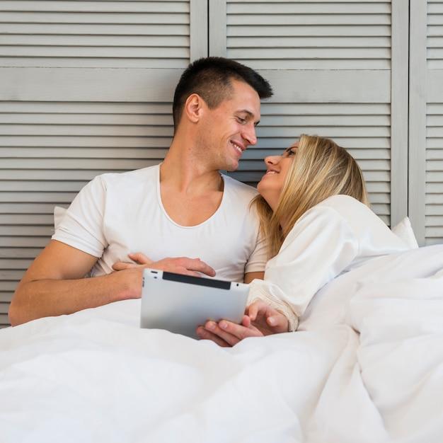 Jovem casal sorridente com tablet debaixo do cobertor na cama Foto gratuita