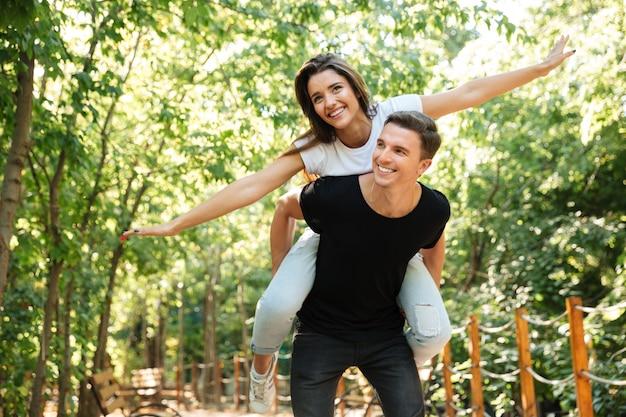 Jovem casal sorridente, desfrutando de cavalinho e rindo Foto gratuita