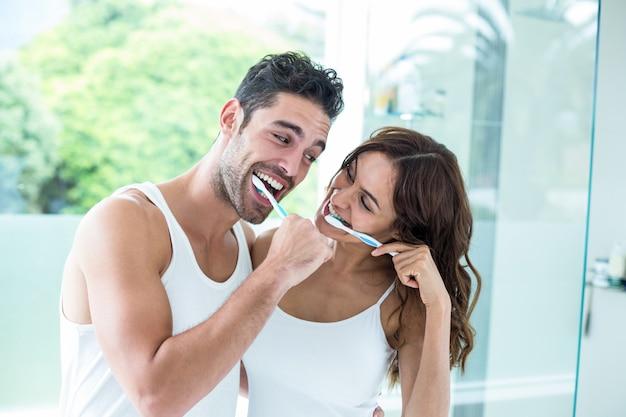 Jovem casal sorrindo enquanto escova os dentes Foto Premium