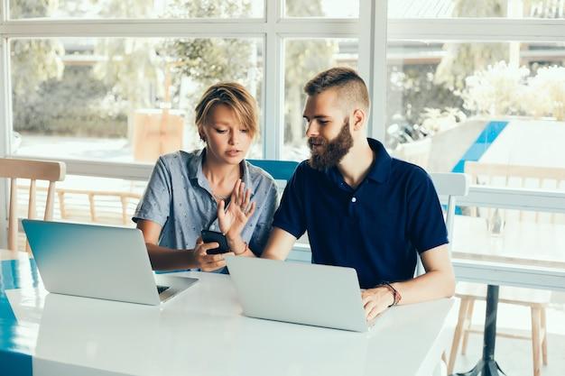 jovem casal trabalhando em laptops em um café fazendo um projeto, conferindo, freelancers Foto gratuita