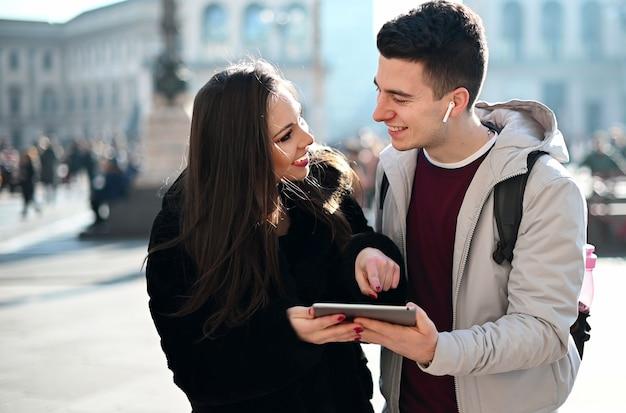 Jovem casal usando um tablet digital ao ar livre enquanto visitava uma cidade Foto Premium