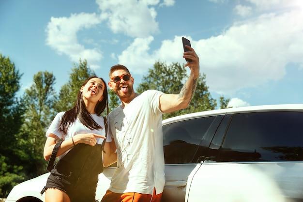 Jovem casal vai tirar férias no carro num dia ensolarado de verão. mulher e homem fazendo selfie na floresta e parece feliz. conceito de relacionamento, férias, verão, feriado, fim de semana, lua de mel. Foto gratuita