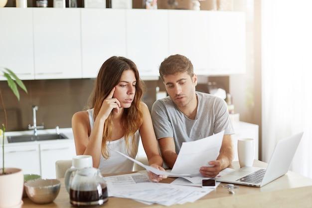 Jovem casal verificando seu orçamento familiar Foto gratuita