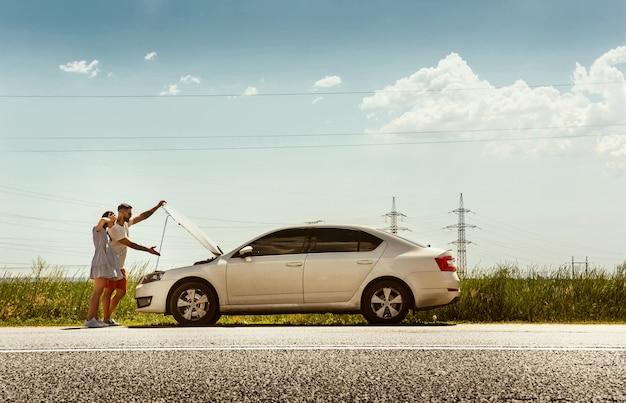 Jovem casal viajando no carro em um dia ensolarado Foto gratuita