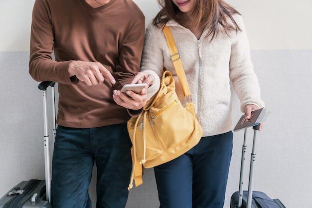 Jovem casal viajante com bagagem e mochila usando smartphone no aeroporto Foto Premium