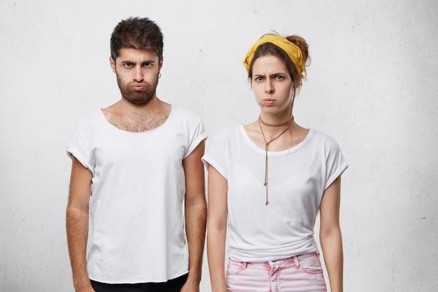 Jovem casal zangado com expressões amuadas, assoando o rosto em desespero, tendo relacionamentos ruins Foto gratuita