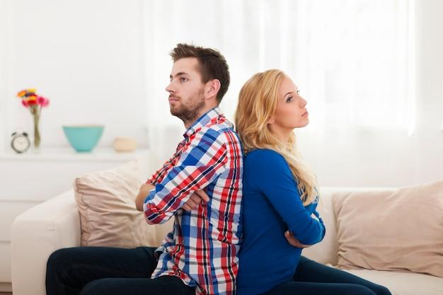 Jovem casal zangado sentado de costas para a casa Foto gratuita