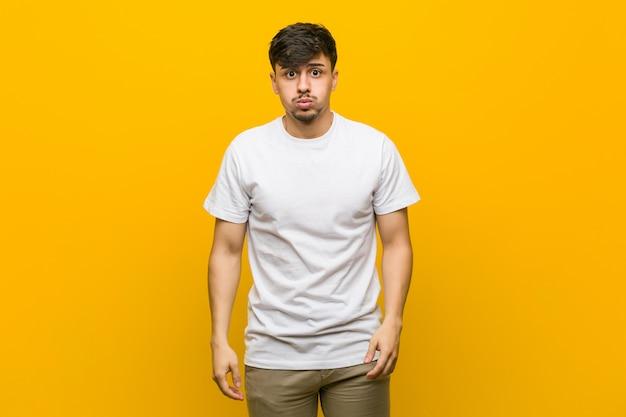 Jovem casual latino-americano sopra as bochechas, tem expressão cansada. expressão facial. Foto Premium