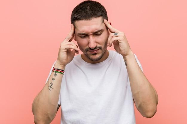 Jovem casual tocando os templos e tendo dor de cabeça. Foto Premium