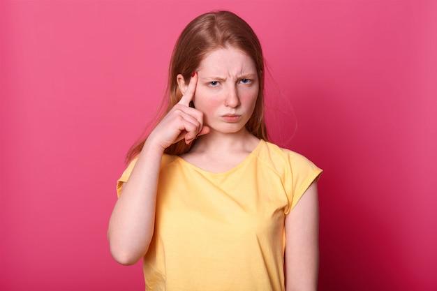 Jovem caucasiana focada tocando templos com os dedos indicadores e franzindo a testa, tem expressão facial pensativa Foto gratuita