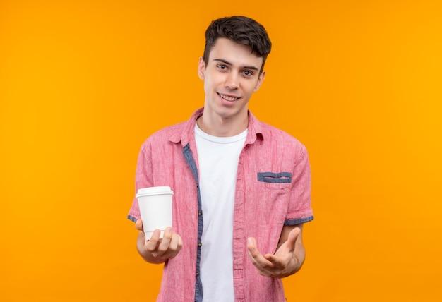 Jovem caucasiano sorridente, vestindo uma camisa rosa, segurando uma xícara de café com a mão estendida sobre um fundo laranja isolado Foto gratuita