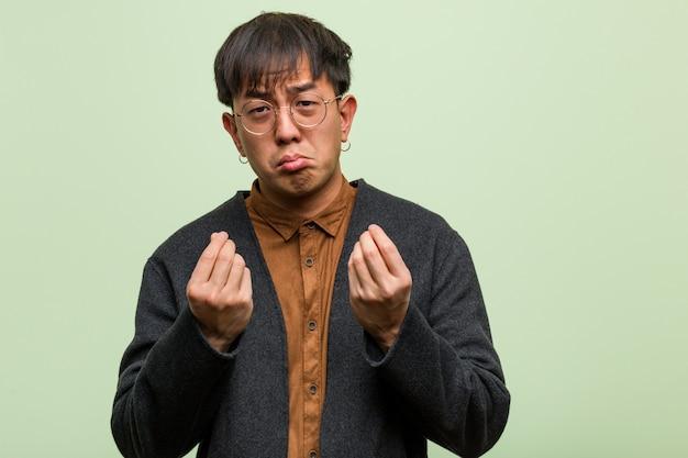 Jovem chinês contra uma parede verde Foto Premium