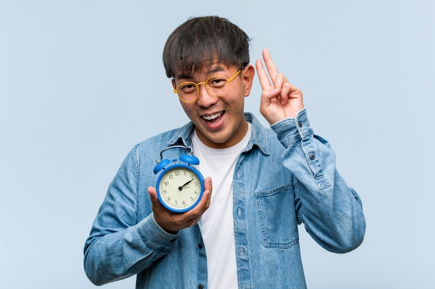 Jovem chinês segurando um despertador divertido e feliz fazendo um gesto de vitória Foto Premium