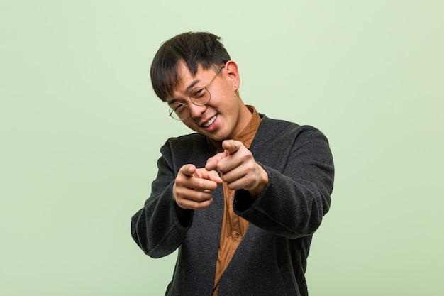 Jovem chinês, vestindo um estilo de roupas legais contra uma parede verde Foto Premium