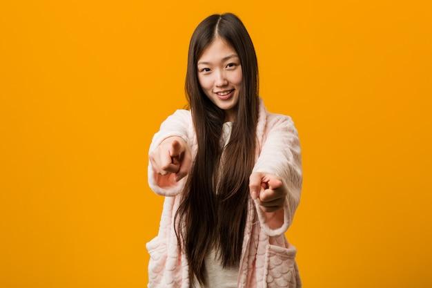 Jovem chinesa em sorrisos alegres de pijama, apontando para a frente. Foto Premium