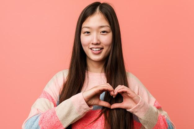 Jovem chinesa legal sorrindo e mostrando uma forma de coração com ele as mãos. Foto Premium