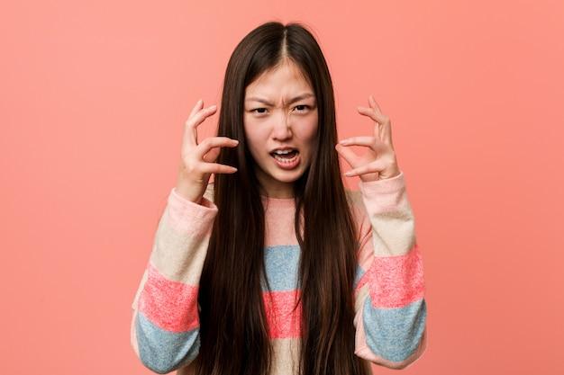 Jovem chinesa legal virada gritando com as mãos tensas. Foto Premium