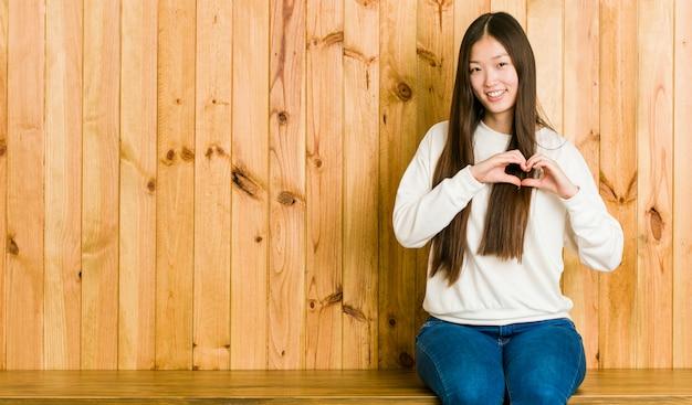 Jovem chinesa sentado em um lugar de madeira, sorrindo e mostrando uma forma de coração com as mãos. Foto Premium