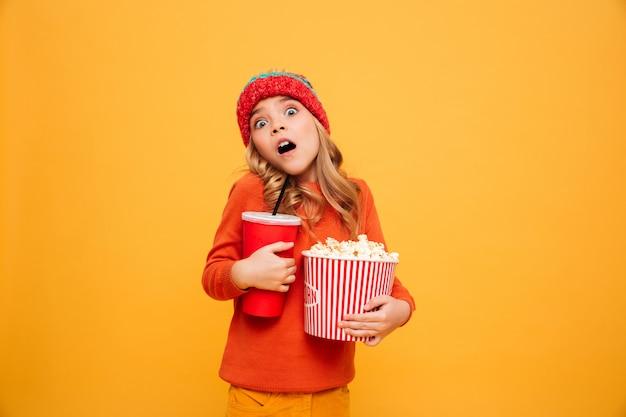 Jovem chocada na camisola e chapéu segurando pipoca e copo de plástico enquanto olha para a câmera sobre laranja Foto gratuita