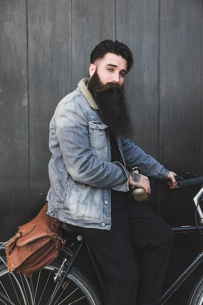 Jovem, ciclista, sentando, com, fones, e, saco, olhando câmera Foto gratuita